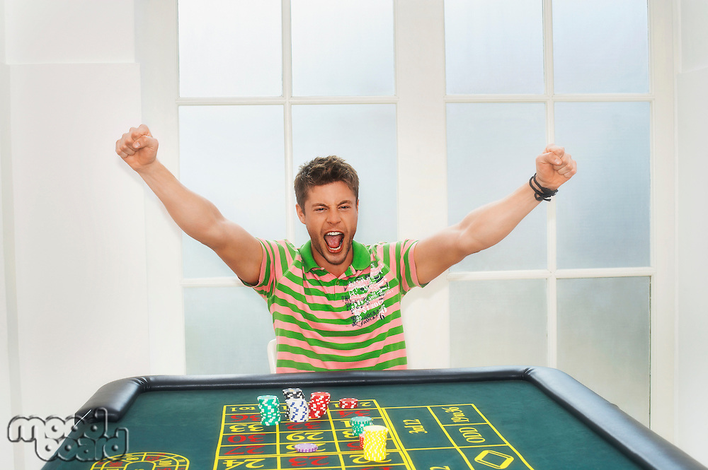Young Man celebrating on roulette table