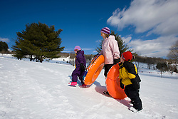 A woman and her two young kids (age 3 and 6) on a sledding hill in Quechee, Vermont. Model Release.