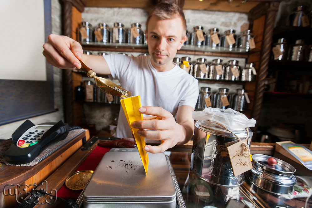 Salesperson scooping ingredient into paper bag at tea store