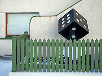 Green fence and a dice outside an appartment house in Vestmannaeyjar islands. Iceland.