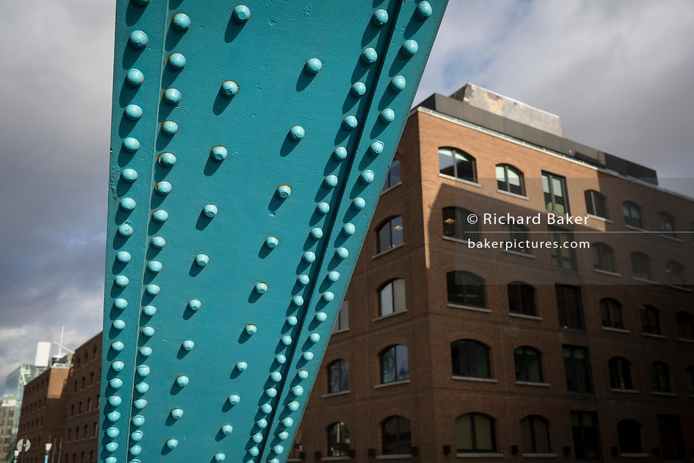 Eighties office architecture and the steel rivets from one of Tower Bridge's steel suspension anchor girders, on 14th December 2017, in the City of London, England.