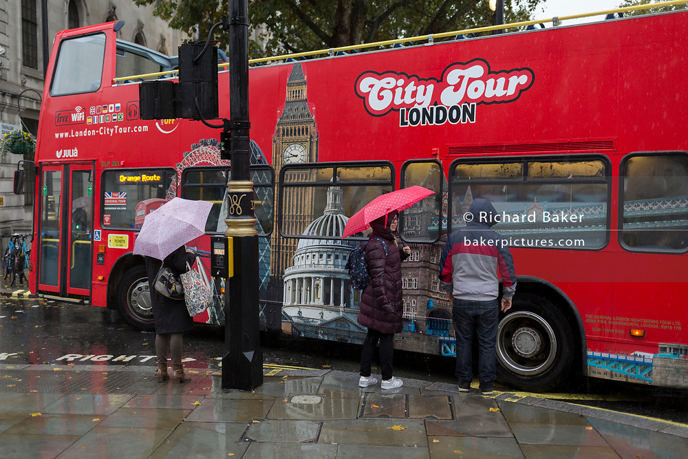 A London city tour bus passes visitors to the capital during heavy rainfall on an autumn afternoon in Trafalgar Square, on 24th October 2019, in Westminster, London, England.