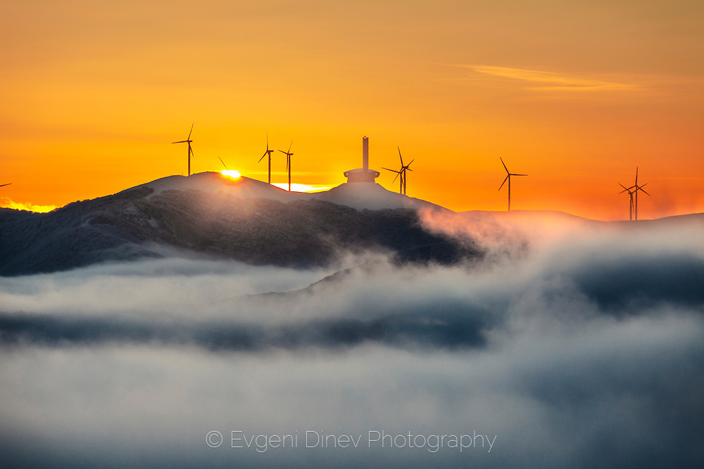 Wind generators around a memorial at sunrise