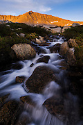Last light on the back of the Four Gables with mountain stream just below Steelhead Lake in the High Sierra mountains over Pine Creek Pass west of Bishop, California, July 2016.