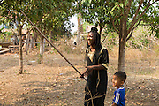 ICS volunteer Tania Tuzizila uses a large stick to pick mangos in the garden of her host home, in the village of in Banteay Char, near Battambang, Cambodia.