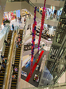 "27 MARCH 2015 - BANGKOK, THAILAND: Shoppers on escalators in ""EmQuartier,"" a new shopping mall in Bangkok.  ""EmQuartier"" is across Sukhumvit Rd from Emporium. Both malls have the same corporate owner, The Mall Group, which reportedly spent 20Billion Thai Baht (about $600 million US) on the new mall and renovating the existing Emporium. EmQuartier and Emporium have about 450,000 square meters of retail, several hotels, numerous restaurants, movie theaters and the largest man made waterfall in Southeast Asia. EmQuartier celebrated its grand opening Friday, March 27.   PHOTO BY JACK KURTZ"