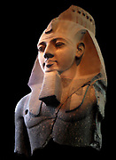 Statue of Ramesses II, the 'Younger Memnon' From the Ramesseum, Thebes, Egypt, 19th Dynasty, about 1250 BC. Ramesses II, who succeeded his father Sethos I in around 1279 BC and ruled Egypt for 67 years. Weighing 7.25 tons, this fragment of his statue was cut from a single block of two-coloured granite. He is shown wearing the nemes head-dress surmounted by a cobra diadem.