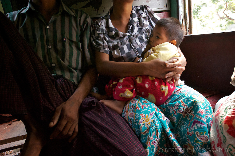A mother breast-feeds her baby on a train trip
