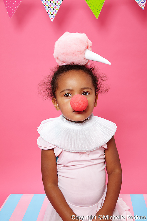 Girl wearing clown nose,collar and cotton candy hat sitting on pink and blue striped bench on pink seamless. Photographed at Photoville Photo Booth September 20, 2015