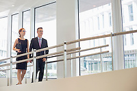 Business people walking by railing in office