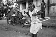 Fillette jouant au hoola hoop dans un camp de travailleurs de la canne-à-sucre..Young girl playing hoolahoop in a workers camp of sugarcane cutters .