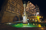 ROTHENBURG OB DER TAUBER, GERMANY - SEPTEMBER 06, 2010: Historic buildings with fountain at the foreground at night in Rothenburg Ob Der Tauber, Germany.