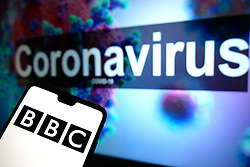 The BBC logo seen displayed on a mobile phone with an illustrative model of the Coronavirus displayed on a monitor in the background. Photo credit should read: James Warwick/EMPICS Entertainment
