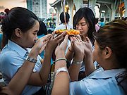 25 NOVEMBER 2015 - BANGKOK, THAILAND:  Thai students huddle in prayer before floating their krathong in the Chao Phraya River during Loy Krathong at Wat Yannawa in Bangkok. Loy Krathong takes place on the evening of the full moon of the 12th month in the traditional Thai lunar calendar. In the western calendar this usually falls in November. Loy means 'to float', while krathong refers to the usually lotus-shaped container which floats on the water. Traditional krathongs are made of the layers of the trunk of a banana tree or a spider lily plant. Now, many people use krathongs of baked bread which disintegrate in the water and feed the fish. A krathong is decorated with elaborately folded banana leaves, incense sticks, and a candle. A small coin is sometimes included as an offering to the river spirits. On the night of the full moon, Thais launch their krathong on a river, canal or a pond, making a wish as they do so.    PHOTO BY JACK KURTZ