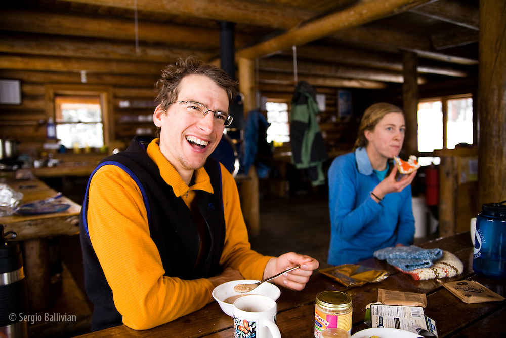 John Heisel and friend have breakfast inside the Peter Estin hut in Colorado during winter.  Hut tours are very popular in Colorado where you enjoy warmth, safety and plenty of ammenities while in the backcountry.