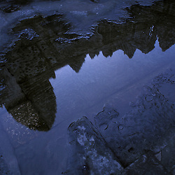 The towers of Angkor Wat temple reflected in a rain puddle in Siem Reap, Cambodia.