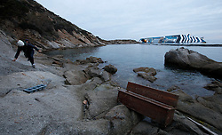 A woman climbs on the rocks past a bench washed ashore from the cruise liner Costa Concordia, which ran aground off the west coast of Italy, at Giglio island January 27, 2012. Costa Cruises has offered to pay 11,000 euros ($14,500) in compensation to each of the more than 3,000 passengers aboard the ship that capsized near the island of Giglio two weeks ago, Italian consumer groups said on Friday. <br /> REUTERS/Darrin Zammit Lupi (ITALY)