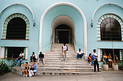 Exterior view of building painted blue in Vedado; Havana Cuba;  with a large arched doorway and long flight of steps,