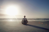 Business man sitting in lotus pose on beach