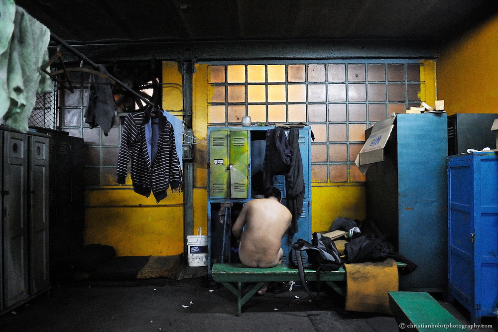 A worker undresses and washes himself at the end of the workday.