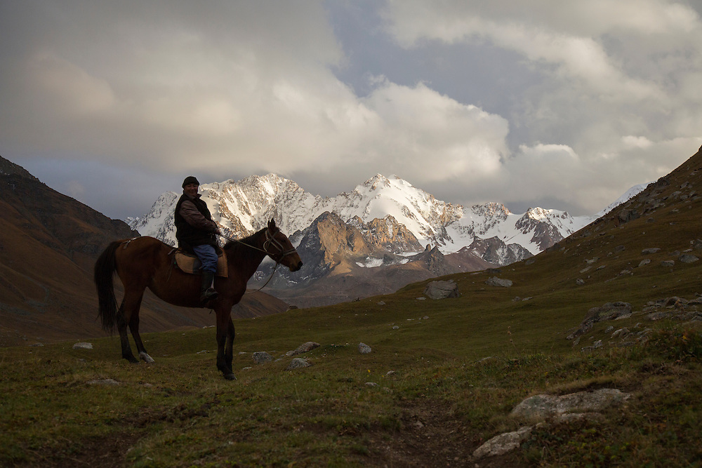 "Nurdin Orozaliev sits on his horse at his camp at the foot of Chok-Tal, a 15 thousand foot peak in the Chon Kemin Valley. It is estimated that most of the glaciers here could ""disappear completely"" by around 2080."