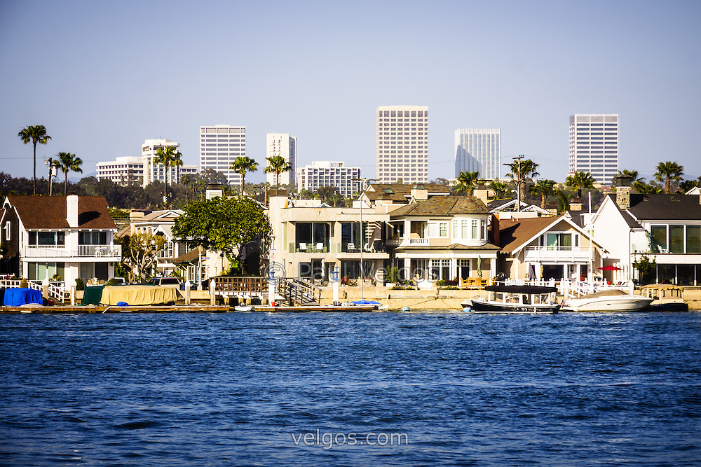 Newport Beach skyline and waterfront homes picture. Photo includes Newport Beach office buildings and waterfront homes along Newport Harbor. Newport Beach is a wealthy city in Orange County California.