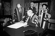 23/04/1964<br /> 04/23/1964<br /> 23 April 1964<br /> Honorary Degrees conferred at the National University of Ireland, Iveagh House, Dublin. <br /> President Eamon de Valera (right) signing the register after the ceremony watched by President Eamon de Valera (right), Chancellor of N.U.I. and Dr. Seamus Wilmot, Registar of the University.<br /> Also present are Dr. Michael Tierney, President of U.C.D. and Mrs Cecil Woodham-Smith (Degree D.Litt.), Distinguished author and historian.