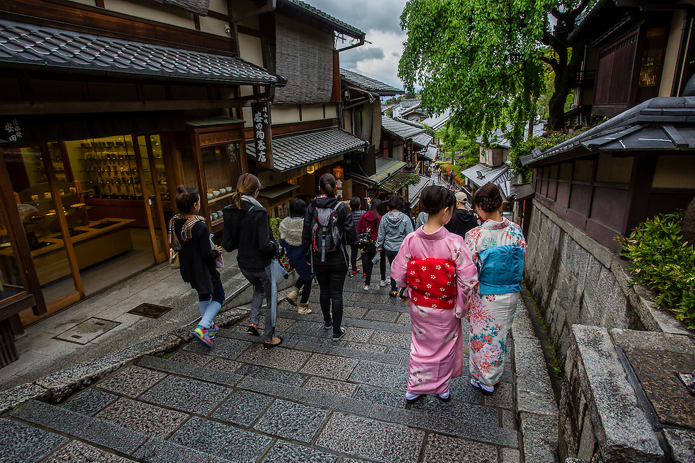 Two young women in Kimono descend Sannenzaka stairs. Kinono rental is part of the tourist experience in Kyoto. Lots of people rent kimono for a day and go walking around the old traditional streets in Higashiyama dstrict.