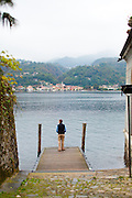 A man stands on the end of a dock on Isola San Giulio, looking out over Lake Orta at the village of Pella, Piedmont, Italy.