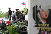 Protestors sit on an elephant statue in Lumpini Park during the Red Shirts anti-government protest in the Silom area of Bangkok. On the right is a defaced poster of Thailand Prime Minister Abhisit Vejjajiva.