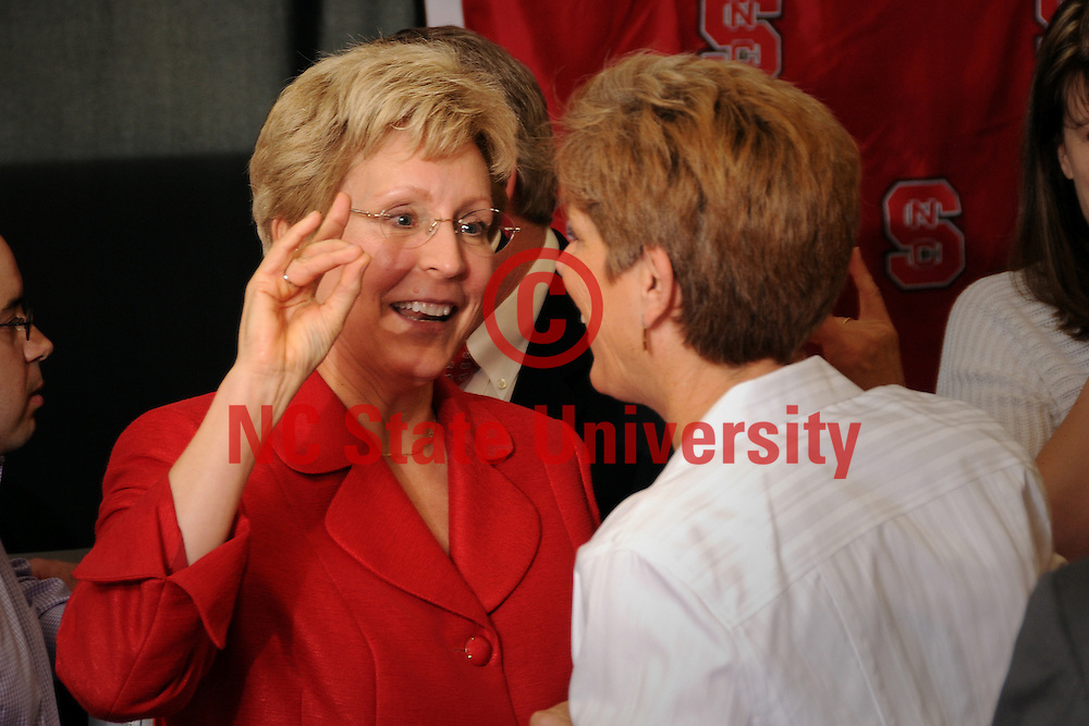 """New NC State Athletics Director Debbie Yow (left) gets a quick tutorial on making the """"wolf"""" sign with her fingers from sister Susan Yow."""