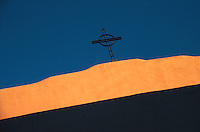 Cross and church wall against dark blue sky Santa Fe New Mexico USA