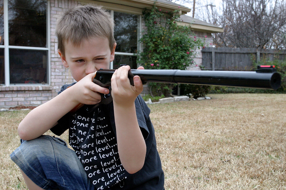 Young boy shooting a BB gun, Dallas, Texas, USA
