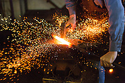 A blacksmith shapes red hot steel using a sledgehammer and anvil in an metal work shop in Charleston, SC