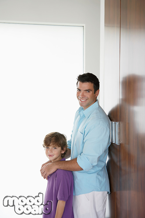Father and son (7-9) leaning on wardrobe and smiling