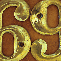 Slightly tarnished brass screw-on house numbers 69 lying on brown metal surface