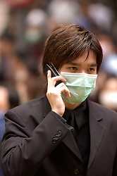Businessman wearing a mask and speaking on telephone during SARS epidemic in Hong Kong in 2003