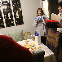 Lauren Wood | Buy at photos.djournal.com<br /> Mimi VanDevender gives Lindsey Nelson Newhall, 16, a gift on Dec. 6, the first night of Hanukkah at VanDevender's Tupelo home. It is a tradition to give small gifts over the eight day holiday.