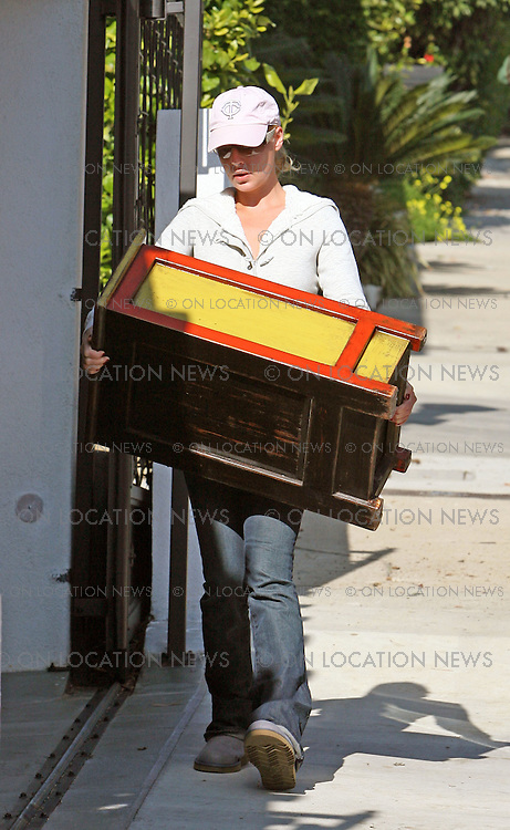 LOS ANGELES, CALIFORNIA - Thursday 10th January 2008. NON EXCLUSIVE: Newly wed Katherine Heigl carries a cabinet into her mum's house. Heigl then called into her new house with husband Josh Kelly.Photograph: David Buchan/On location News. Sales: Eric Ford 1/818-613-3955 info@OnLocationNews.com..