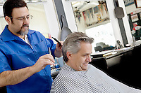 Mature barber giving a haircut to customer