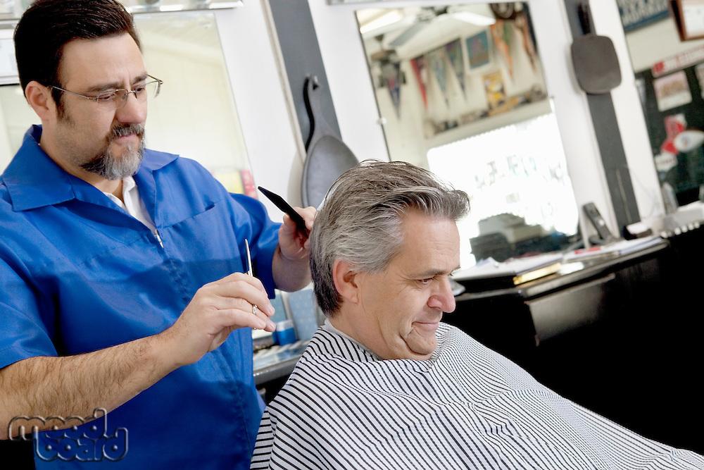Mature barber giving a haircut to customer