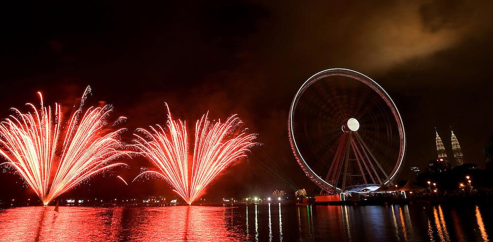 A 60-metre-high Ferris wheel stands against Petronas Towers as fireworks explode, Kuala Lumpur, Malaysia.
