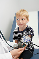 Doctor taking blood pressure of boy