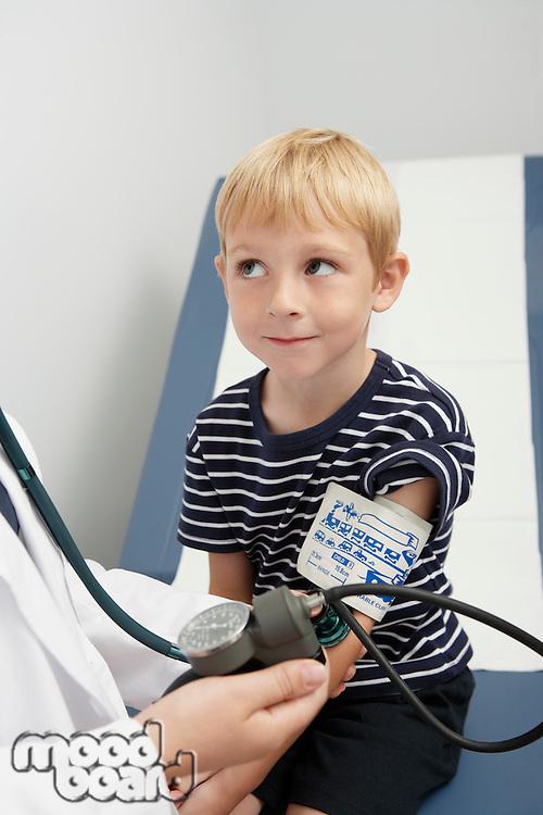 Doctor taking blood pressure of boy