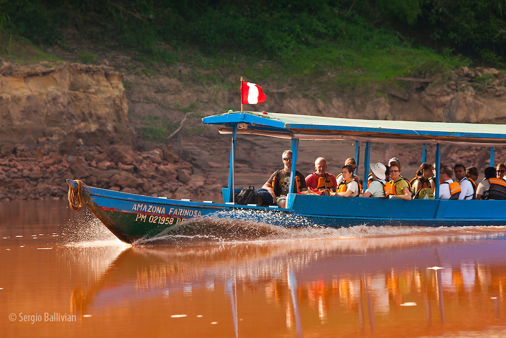 Tourists travel to lodges deep in the jungle via motorized boats with canopy on the Tambopata River in Tambopata NP in the Peruvian Amazon.