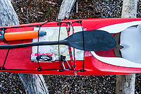 Detail of maps and gear on a sea kayak. Skagit Island State Park, Washington, USA.
