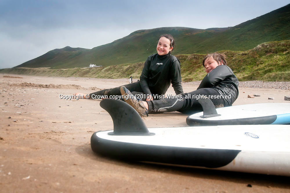 Boy and girl resting on beach after surfing<br /> Rhossili<br /> Gower Peninsula<br /> Surfing<br /> Activities and Sports