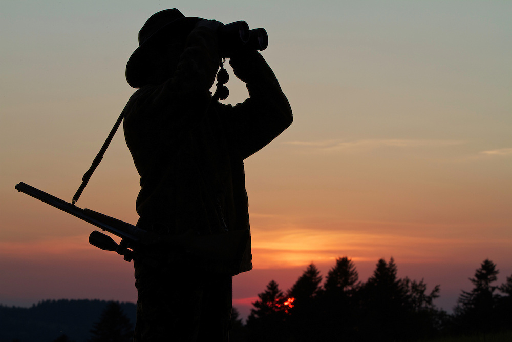 Hunter watching through binoculars. Leszczowate, Bieszczady region, Poland.