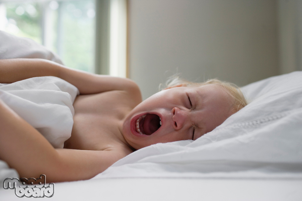 Young girl (1-2) lying in bed yawning