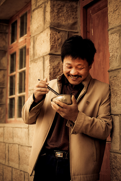 happy man eating bowl of rice,Zhoushan,China